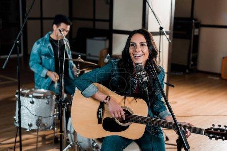 Photo pour Foyer sélectif de belle femme jouant la guitare et chantant tandis que le musicien mélangé de course jouant la batterie - image libre de droit