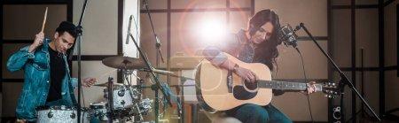 Photo pour Tir panoramique de la femme attirante jouant la guitare tandis que le musicien mélangé de course jouant la batterie dans le studio d'enregistrement - image libre de droit