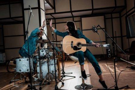 Photo pour De jeunes musiciens multiculturels inspirés donnant cinq étoiles dans un studio d'enregistrement - image libre de droit