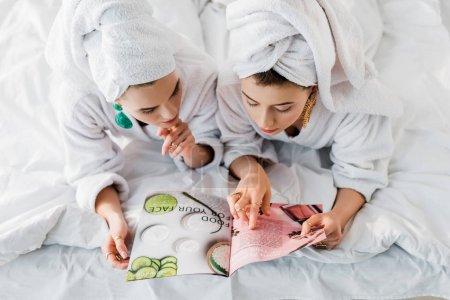 Photo for Overhead view of stylish women in bathrobes, earrings and with towels on heads reading magazine together while lying in bed - Royalty Free Image