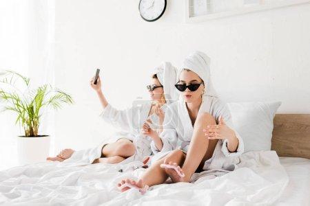 Photo pour Femmes élégantes dans des peignoirs, des lunettes de soleil, des serviettes et des bijoux se trouvant dans le lit, faisant la pédicure et prenant le selfie - image libre de droit
