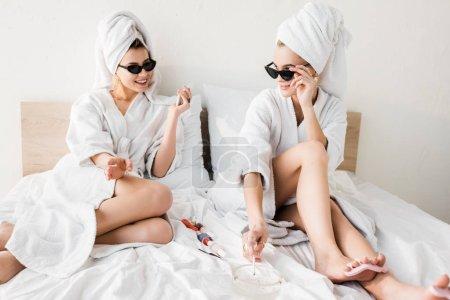 Photo pour Femmes élégantes heureuses dans des peignoirs et des lunettes de soleil, des serviettes et des bijoux se trouvant dans le lit, faisant la pédicure et fumant près du cendrier - image libre de droit