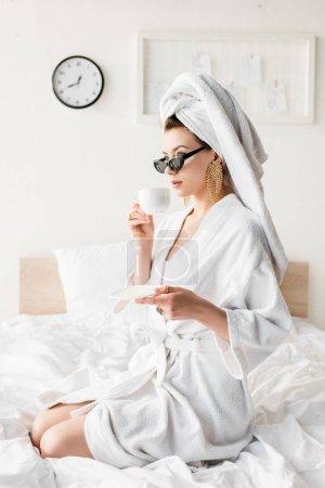 Photo pour Femme élégante en peignoir et lunettes de soleil, serviette et bijoux boire du café au lit - image libre de droit
