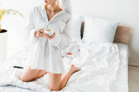cropped view of young stylish woman in shirt, jewelry and with towel on head sitting on bed while drinking coffee