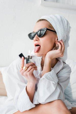 Photo pour Jeune femme élégante en bijoux et lunettes de soleil avec une serviette sur la tête sortant de la langue près du feu d'un briquet - image libre de droit