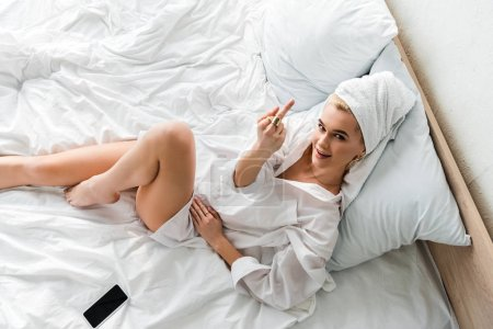 top view of barefoot woman in jewelry with towel on head lying in white bed near smartphone and showing middle finger