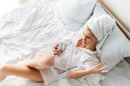 Photo pour Vue supérieure de la femme insatisfaite dans des bijoux avec la serviette sur la tête se trouvant dans le lit blanc et utilisant le smartphone - image libre de droit