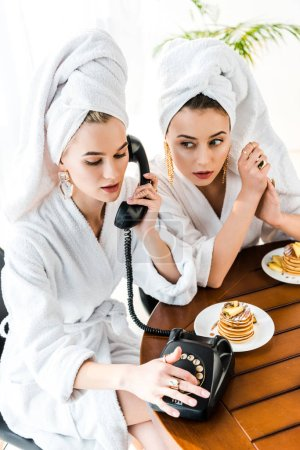 Foto de Stylish women in bathrobes and jewelry with towels on heads using retro telephone while having breakfast - Imagen libre de derechos