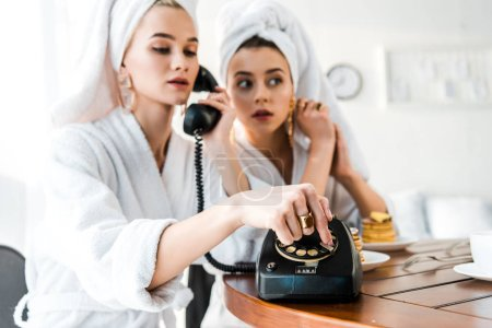 Foto de Selective focus of stylish women in bathrobes and jewelry with towels on heads using retro telephone while sitting at table - Imagen libre de derechos