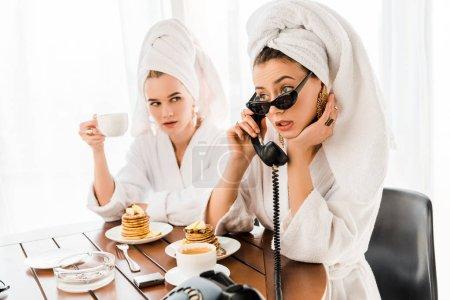 Foto de Mujer elegante en albornoz, gafas de sol y joyas con toalla en la cabeza usando teléfono retro mientras desayuna con un amigo - Imagen libre de derechos