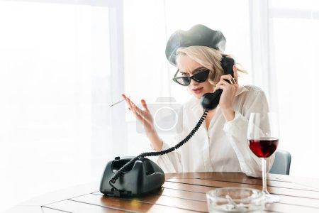 Foto de Elegante mujer rubia insatisfecha en la beret negro y gafas de sol fumando cigarrillo mientras habla en el teléfono retro cerca de una copa de vino tinto - Imagen libre de derechos