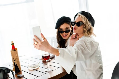 Photo for Elegant brunette and blonde women in black berets and sunglasses drinking red wine and taking selfie while pouting lips and sticking out tongue - Royalty Free Image