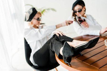 Foto de Enfoque selectivo de la mujer elegante en la beret negro y gafas de sol con las piernas en la mesa clinking con el amigo - Imagen libre de derechos