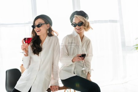 Photo for Elegant happy brunette and blonde women in black berets and sunglasses laughing and drinking red wine - Royalty Free Image