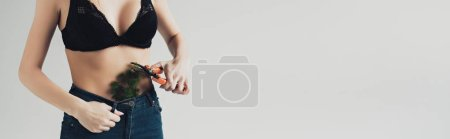 Photo for Panoramic shot of woman in black bra cutting plant in pants with secateurs isolated on grey - Royalty Free Image