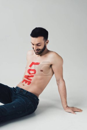 Photo for Smiling shirtless man with inscription on body sitting on grey - Royalty Free Image