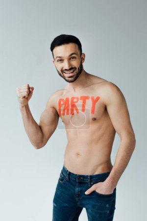 Photo for Smiling shirtless man with inscription on body showing yes gesture on grey - Royalty Free Image