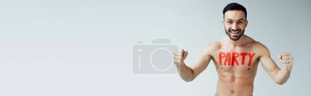 Photo for Panoramic shot of smiling shirtless man with inscription on body showing yes gesture on grey - Royalty Free Image
