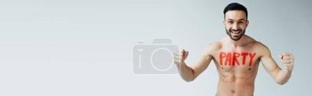 Photo pour Plan panoramique d'un homme torse nu souriant avec inscription sur le corps montrant un geste oui sur le gris - image libre de droit