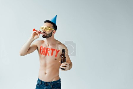 Foto de Shirtless man with party blower holding bottle of beer isolated on grey - Imagen libre de derechos