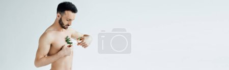 Photo for Panoramic shot of handsome bearded man cutting plant on chest with scissors on grey - Royalty Free Image