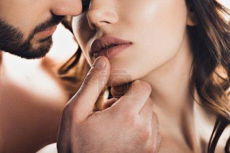 Photo pour Vue recadrée de l'homme barbu toucher doucement petite amie isolée sur blanc - image libre de droit