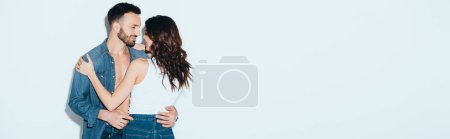 Photo for Panoramic shot of smiling couple embracing on grey - Royalty Free Image