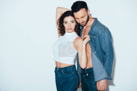 Photo for Stylish couple in jeans standing together on grey - Royalty Free Image