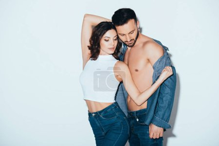 Photo for Pretty young woman in jeans undressing boyfriend on grey - Royalty Free Image