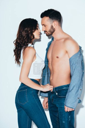 Photo for Sensual young woman unzipping jeans on boyfriend on grey - Royalty Free Image
