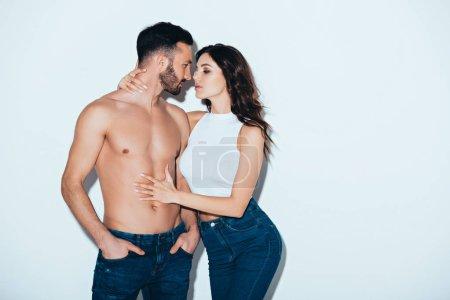 Foto de Pretty young woman embracing shirtless boyfriend on grey - Imagen libre de derechos