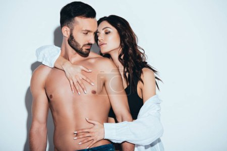 Photo for Girlfriend in white shirt embracing with boyfriend on grey - Royalty Free Image