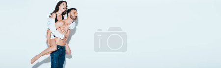 Photo for Panoramic shot of smiling handsome man carrying girlfriend piggyback on grey - Royalty Free Image