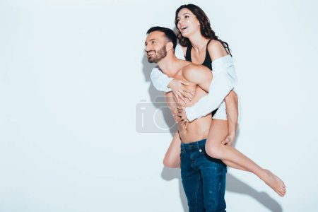 Photo for Smiling handsome man carrying girlfriend piggyback on grey - Royalty Free Image