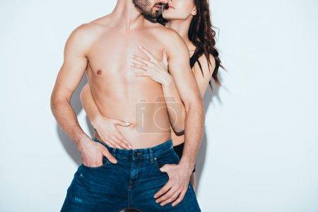 Foto de Cropped view of sensual woman embracing bearded shirtless man on grey - Imagen libre de derechos