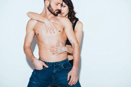 Foto de Sensual woman embracing bearded shirtless man on grey - Imagen libre de derechos