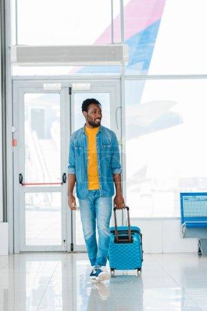 Photo pour Sourire heureux homme afro-américain marche avec valise le long de la salle d'attente à l'aéroport - image libre de droit