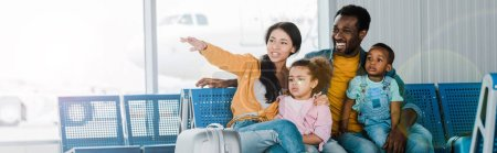 Photo for Panoramic shot of smiling african american family with baggage and kids sitting in airport while mother pointing with finger away - Royalty Free Image