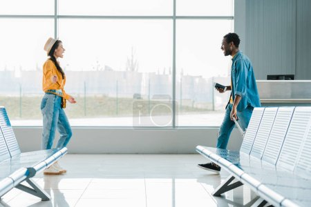 Photo for Side view of happy african american man walking towards smiling girlfriend in airport - Royalty Free Image