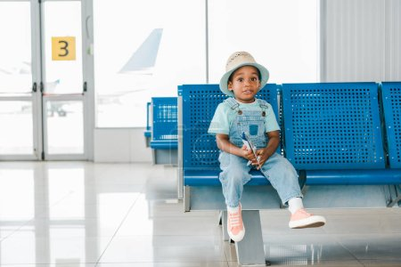 Photo for Adorable african american boy sitting with toy plane in airport - Royalty Free Image