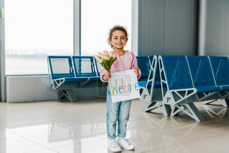 Photo for Smiling african american kid standing in waiting hall in airport and holding tulips and placard with welcome lettering - Royalty Free Image