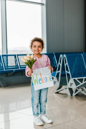 Photo for Happy african american kid standing in waiting hall in airport and holding tulips and placard with welcome lettering - Royalty Free Image