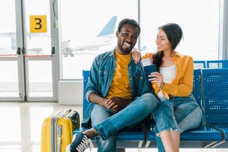 Foto de Feliz pareja afroamericana sentada en la sala de salidas con equipaje y boletos aéreos en el aeropuerto - Imagen libre de derechos