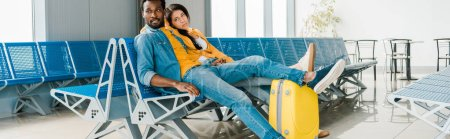 Photo for Panoramic shot of tired african american couple sitting in departure lounge with suitcase and waiting for flight - Royalty Free Image