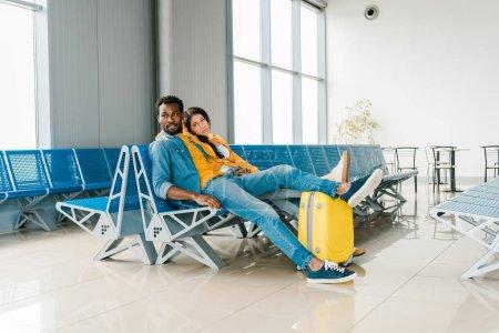 Photo pour Épuisé couple afro-américain assis dans le salon de départ avec valise et en attente de vol - image libre de droit