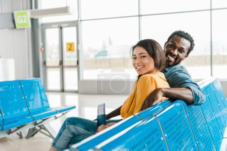 Photo for Happy african american couple sitting in departure lounge with passports and air tickets - Royalty Free Image