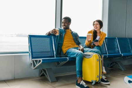 Photo for Happy african american couple sitting in departure lounge with coffee to go and yellow travel bag - Royalty Free Image