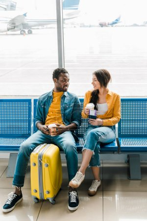 Photo for Smiling african american couple sitting in departure lounge with coffee to go and yellow suitcase - Royalty Free Image