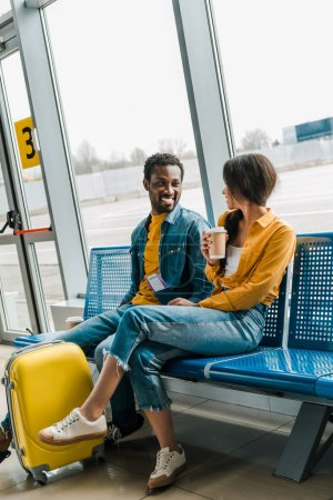 Photo for Happy african american couple sitting in departure lounge with coffee to go and yellow suitcase and looking at each other - Royalty Free Image