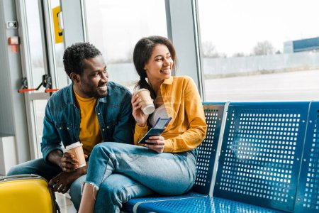 Photo for Happy african american couple sitting in departure lounge with coffee to go and air tickets and looking at window - Royalty Free Image